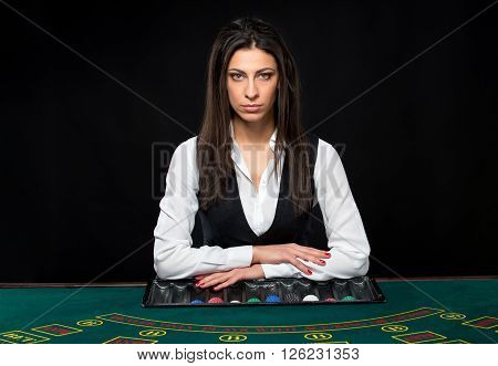 The beautiful girl, dealer, behind a table for game in poker. the dealer deals the cards. He is looking at the camera
