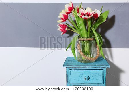 Bouquet of variegated tulips on blue table near striped wall