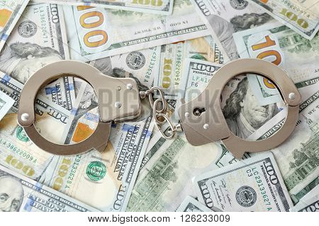 Handcuffs on dollar banknotes. Corruption concept