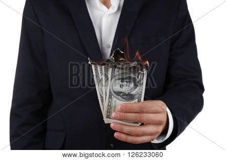 Man in suit holding burning dollar banknotes on white background