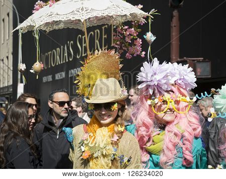NEW YORK - MAR 27 2016: People wearing fancy outfits and decorative Easter bonnets walk along 5th Avenue on Easter Sunday for the traditional Easter Bonnet Parade in Manhattan on March 27, 2016.