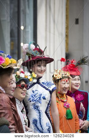NEW YORK - MAR 27 2016: A group of Asian women wearing fancy Easter outfits and bonnets pose for pictures on 5th Ave Easter Sunday at the traditional Easter Bonnet Parade in Manhattan, March 27, 2016.