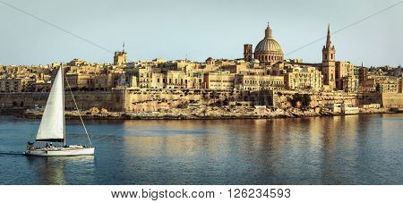 panoramic view of Valetta over sunset and with a sail boat. Malt