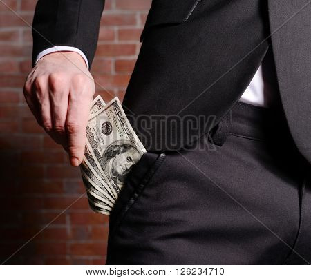 Man getting dollar banknotes out of suit pocket on brick wall background
