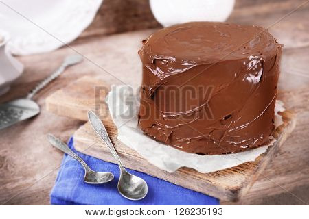 Chocolate cake with two spoons and blue tablecloth on a wooden boards background