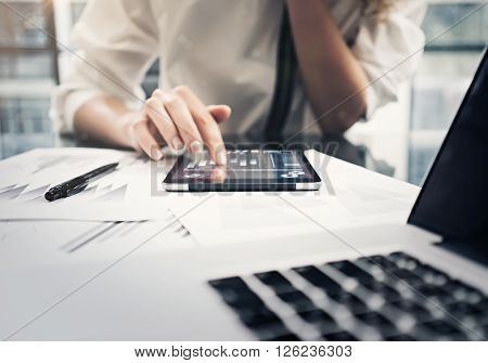 Analytical department working process. Closeup photo business woman reading analytical report modern tablet. Female hand touching screen. Statistics graphics. Film effect ** Note: Shallow depth of field