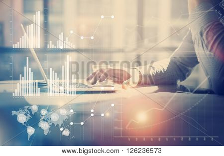Business concept image.Businessman working investment project modern office.Touching pad contemporary laptop. Worldwide connection technology, stock exchanges graphics interface.