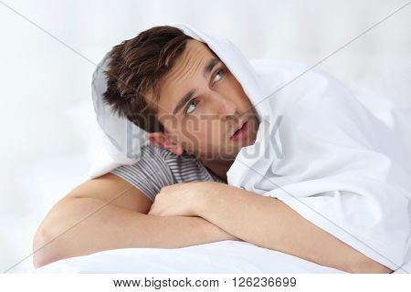 Sleepy young man in bed under a blanket at home
