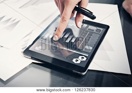 Closeup photo woman working market reports modern tablet and touching screen with worldwide stock exchange icons. Documents for sign on the table. Horizontal.