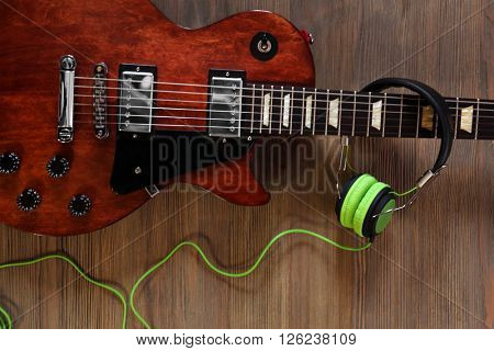Brown electric guitar with headphones on wooden background