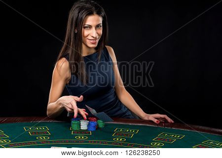 sexy woman with poker cards and chips. Female player in a beautiful black dress. throws a card.
