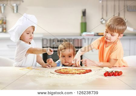 Three little boys making a pizza , close up