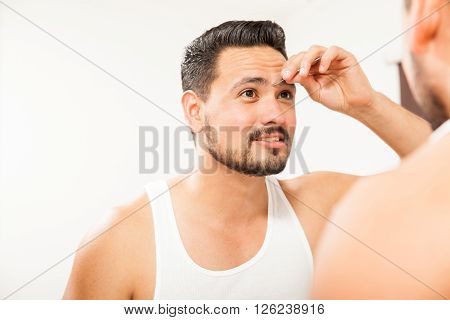 Man Plucking His Eyebrows In The Bathroom