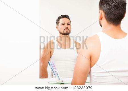 Man Looking At Himself In The Bathroom Mirror