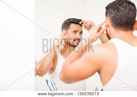 Attractive Guy Combing His Hair In The Bathroom