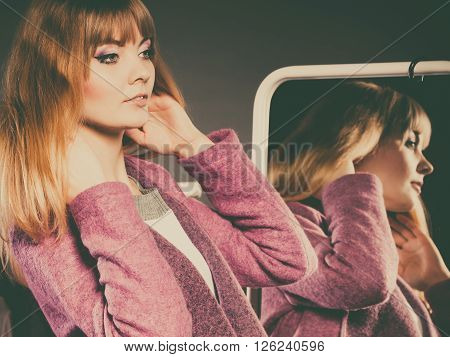 Pretty happy woman in mirror with clothing from new collection wardrobe. Young undecided shopper girl choosing in second hand. Shopping sale concept.