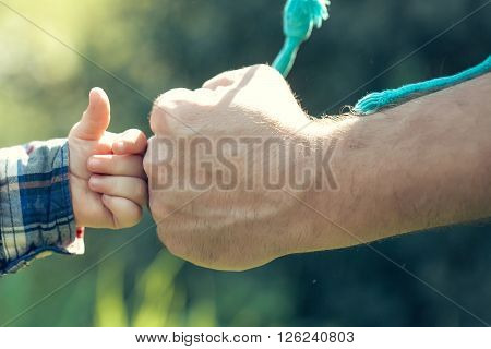 male hand of father lead his child son in summer green grass nature outdoor trust family concept