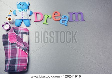Word Dream with pajamas and little toy  on a grey background