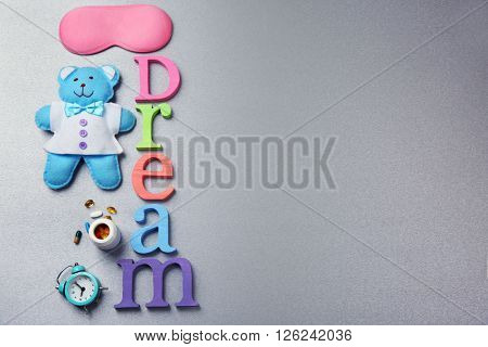 Word Dream with pills, sleeping mask and little toy  on a grey background