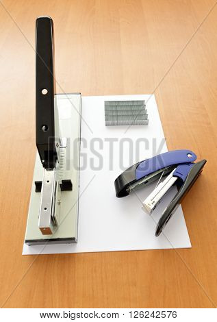 Big and small staplers with staples and paper on the table