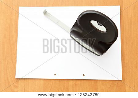 Hole puncher with paper on the office table paper with holes