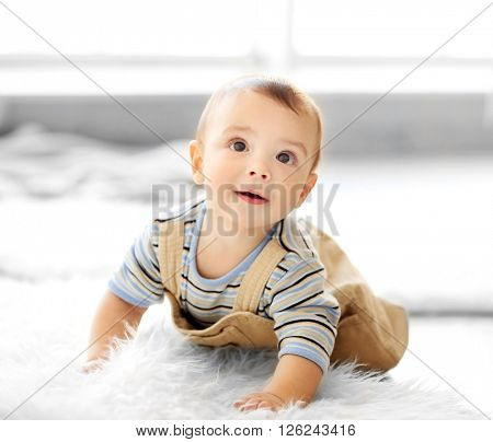 Little baby boy crawling on the floor at home