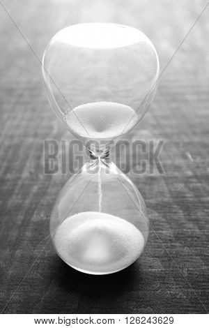 Sand hourglass on wooden background