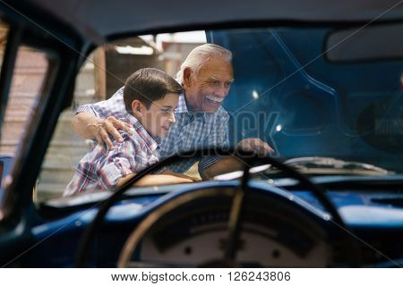 Family and Generation gap. Old grandpa spending time with his grandson. The senior man shows the engine of a vintage car from the 60s to the preteen child. They smile happy. Viewed from the interior of the car