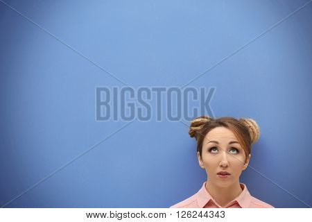 Attractive young blond girl  against blue wall.