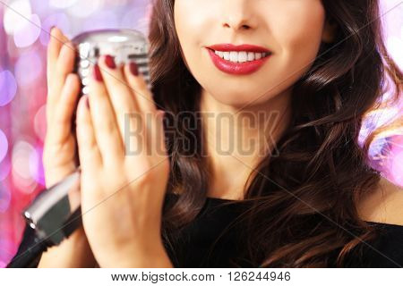 Young beautiful brunette with retro microphone against bright glitter background, close up