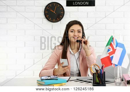 Young woman talking on headset in the office of travel company