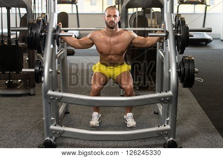 Young Man Doing Exercise Barbell Squat