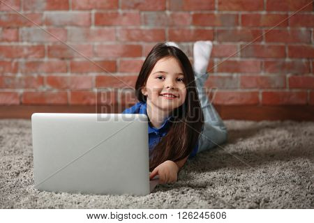 Little girl with laptop on fur carpet against brick wall background