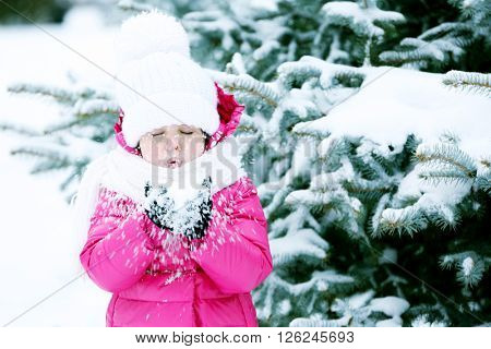 Little girl with winter clothes having fun in snowy park outdoor