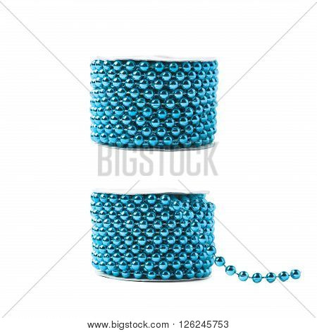 Small blue beads garland thread on a reel isolated over the white background, set of two different foreshortenings