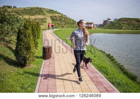 Photo of happy long-haired young blonde woman doing running activities with her dog.