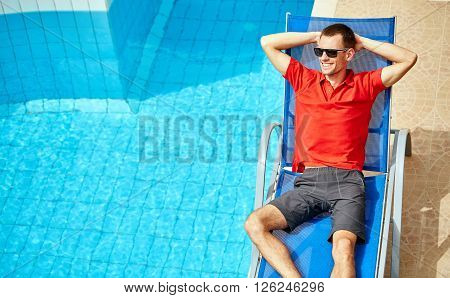 young man relaxing on the chaise-longue near the pool. man wearing in red polo shirt and sunglass