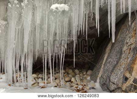 Grottoes and cracks in the rock with icicles. Beautiful winter landscape in the Lake Baikal.