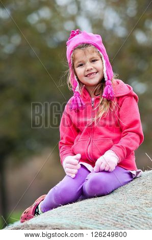 Young adorable girl in toboggan and gloves sitting on a bale of hay outdoors in the cold.
