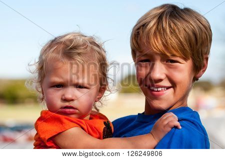 Close up portrait of young boy holding a cute adorable little toddler girl with curly blonde hair.