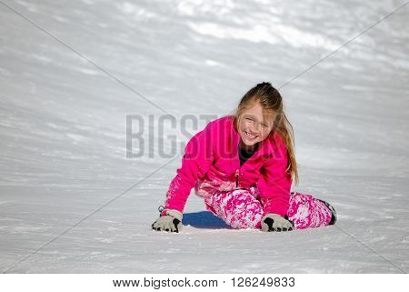Pretty girl in pink playing in the snow having fun and laughing with copyspace.