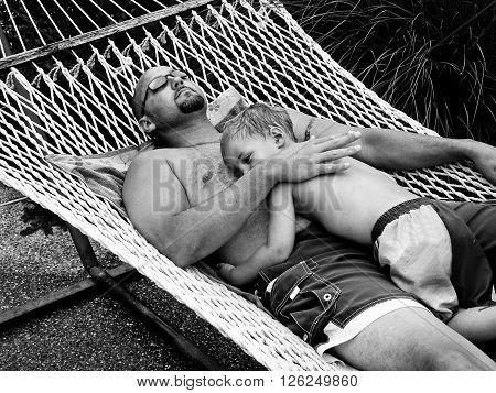 Black and white photo of father and son laying on hammock.