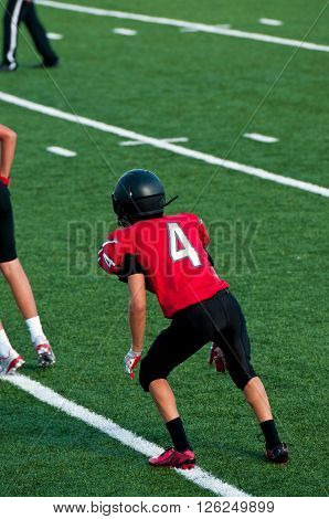 Teenage football boy on the field during a game.