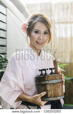 Spa onsen series : Asian woman in yukata holding wooden bucket