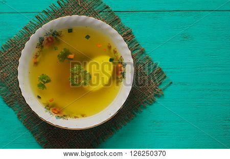 Clear Soup With Vegetables In Plate On Wooden Table .rustic Style