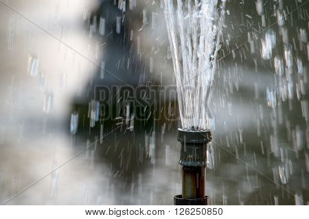 Close-up of a public water fountain gushing a powerful stream of water. Horizontal orientation.