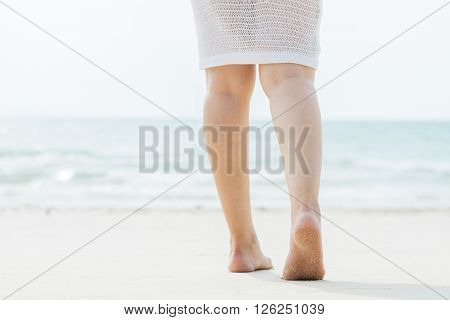 Lifestyle series : Asian woman walking into the sea, focus at the sole