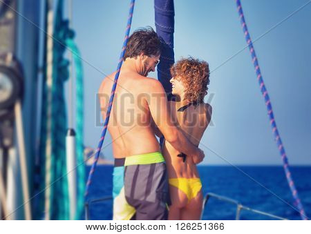 Back side of cheerful young lovers having fun on sailboat traveled along sea, enjoying romantic summer adventure, love and happiness concept
