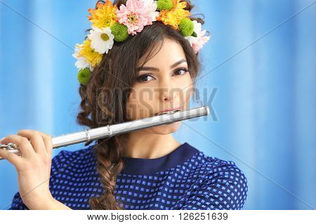 Beautiful young woman with flute on blue curtains background