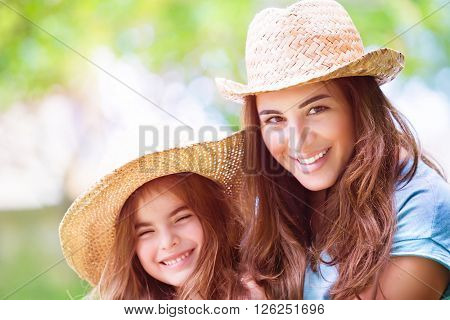 Portrait of joyful young mother with cute cheerful daughter wearing same straw hats and playing outdoors, laughing and looking on each other, portrait of a happy family enjoying life